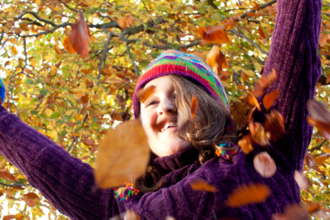 Girl throwing autumn leaves in the air